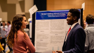 undergraduate students presenting research at NCUR